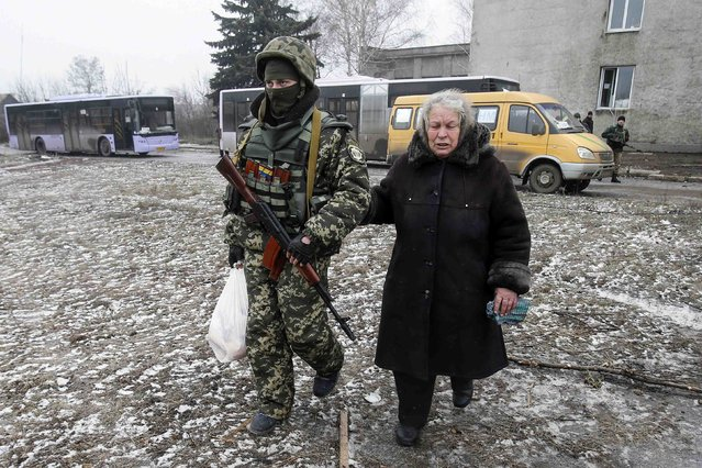 A Ukrainian serviceman helps a woman to carry her bag of humanitarian aid near a delivery point in the government forces-controlled town of Debaltseve, Donetsk region February 6, 2015. (Photo by Maxim Shemetov/Reuters)