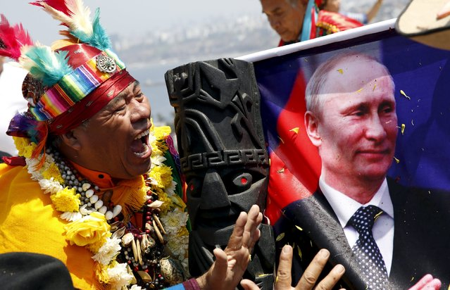 Peruvian shamans holding a poster of Russia's President Vladimir Putin perform a ritual of predictions for the new year at Morro Solar hill in Chorrillos, Lima, Peru, December 29, 2015. (Photo by Mariana Bazo/Reuters)