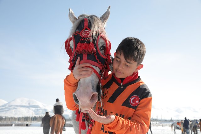 Thirteen-year-old Muhammed Rasit, the youngest member of Uzmanlar, (Experts) sports club, cuddles his horse prior to a game of Cirit, a traditional Turkish equestrian sport that dates back to the martial horsemen who spearheaded the historical conquests of central Asia's Turkic tribes, between the Comrades and the Experts local sporting clubs, in Erzurum, eastern Turkey, Friday, March 5, 2021. (Photo by Kenan Asyali/AP Photo)