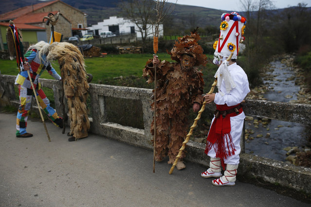 People dressed in costumes have a break while marching during the Vijanera Festival, in the small village of Silio, northern Spain, Sunday, January 3, 2016. The Vijanera masquerade, of pre-Roman origin, is the first carnival of the year in Europe symbolizing the triumph of good over evil and involving the participation of crowds of residents wearing different masks, animal skins and brightly coloured clothing with its own complex function and symbolism and becoming the living example of the survival of archaic cults to nature. (Photo by Francisco Seco/AP Photo)