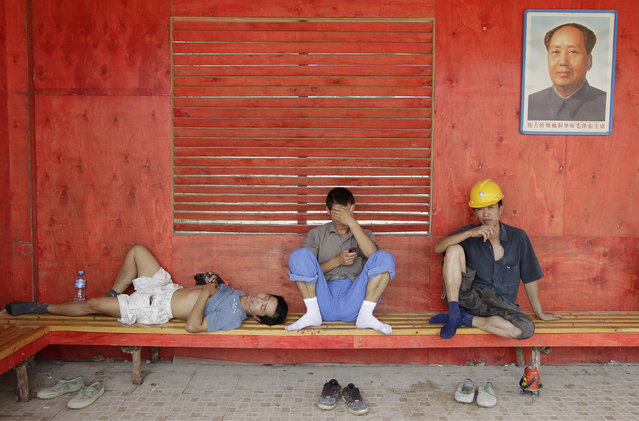 Workers rest on a bench under a portrait of Chairman Mao at a construction site in Wuhan, Hubei province, July 19, 2012. (Photo by Reuters/Stringer)