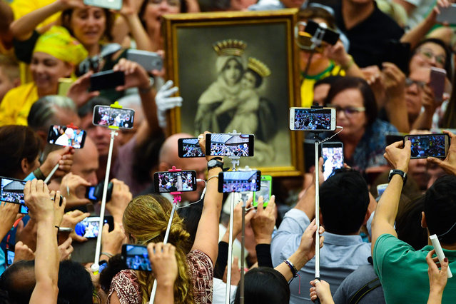 The faithful, holding selfie sticks and mobile phones, wait for the Pope to arrive for his weekly general audience in Paul VI hall on August 22, 2018 at The Vatican. (Photo by Vincenzo Pinto/AFP Photo)