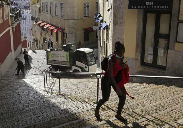 """In this Wednesday, June 24, 2020 file photo, a woman wearing a face mask walks past workers washing the street in Lisbon's old center. A senior European human rights official is sounding the alarm about a rise in racism and discrimination in Portugal. The Council of Europe's Commissioner for Human Rights, Dunja Mijatović, published a report Wednesday, March 24, 2021 into """"the increasing level of racism and the persistence of related discrimination"""" in the southern European country. (Photo by Armando Franca/AP Photo/File)"""