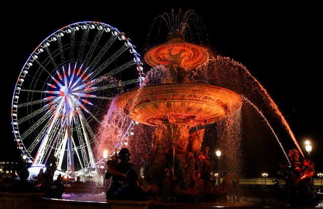 Colored lights are seen on a fountain at the Concorde Place late November 29, 2016 near the giant Ferris wheel as part of illuminations for the Christmas holiday season in Paris, France. (Photo by Jacky Naegelen/Reuters)