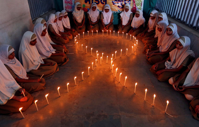 School girls light candles in the shape of a ribbon during a HIV/AIDS awareness campaign ahead of World Aids Day, in Ahmedabad, India November 30, 2016. (Photo by Amit Dave/Reuters)