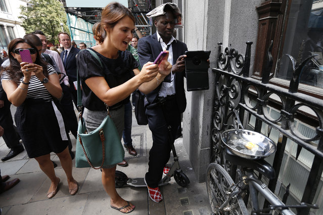 Pedestrians take photographs of an egg frying in a pan using heat from the reflected sunlight off the Walkie Talkie tower in central London September 4, 2013. The Walkie Talkie tower that reflects sunlight at an intensity capable of melting parts of a car became the latest attraction in the city's financial district on Tuesday as the developers acted to find a quick fix. (Photo by Suzanne Plunkett/Reuters)