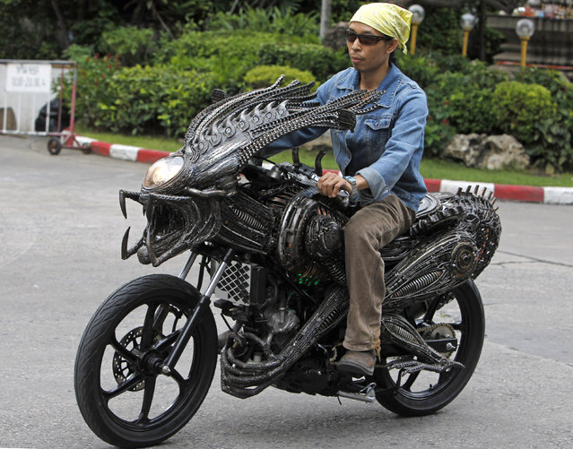 "A worker drives a motorcycle made from recycled materials of spare parts from cars and bicycles at a workshop owned by Roongrojna Sangwongprisarn in Bangkok July 27, 2011. Roongrojna, 54, creates his artworks from recycled spare parts from used cars, motorcycles as well as bicycles. With four shops in Bangkok named ""Ko Art Shop"", Roongrojna also exports his artworks to clients all over the world. (Photo by Sukree Sukplang/Reuters)"