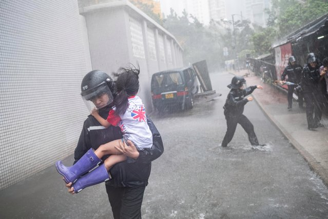 Police officers carry a girl out of a collapsed school on September 16, 2018 in Hong Kong, Hong Kong. City officials raised the storm alert to T10, it's highest level, as Typhoon Mangkhut landed on Hong Kong. The strongest tropical storm of the season so far, with winds as fast as 200 kilometres per hour, Mangkhut has reportedly killed at least 25 people in the Philippines as it continues it's path towards southern China. (Photo by Lam Yik Fei/Getty Images)