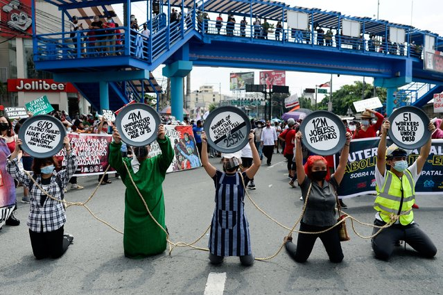 Protesters kneel as they raise placards during a Labor Day protest, in Quezon City, Metro Manila, Philippines, May 1, 2021. (Photo by Lisa Marie David/Reuters)
