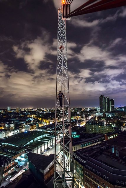 An urban explorer poses on a crane tower in Aldgate East, left over from a mothballed construction site in London. (Photo by Bradley L. Garrett/Barcroft Media)