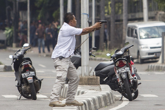A plainclothes police officer aims his gun at attackers during a gun battle following explosions in Jakarta, Indonesia Thursday, January 14, 2016. Attackers set off explosions at a Starbucks cafe in a bustling shopping area in Indonesia's capital and waged gunbattles with police Thursday, leaving bodies in the streets as office workers watched in terror from high-rise buildings. (Photo by AP Photo)