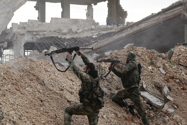 Syrian army soldiers fire their weapons during a battle with rebel fighters at the Ramouseh front line, east of Aleppo, Syria, Monday, December 5, 2016. (Photo by Hassan Ammar/AP Photo)