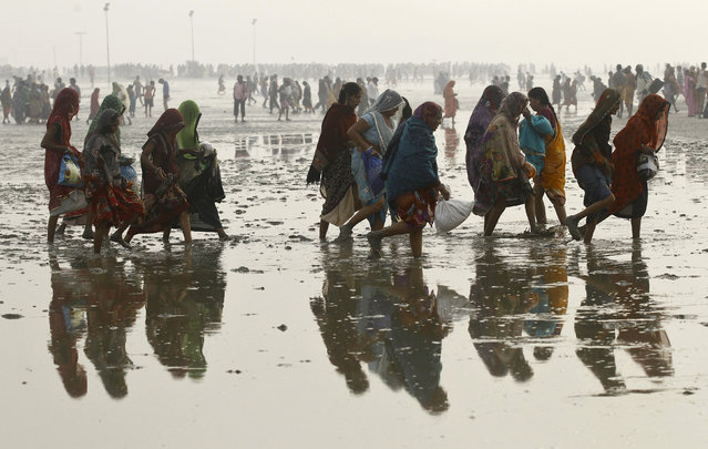 "Hindu pilgrims walk back after taking a dip at the confluence of the river Ganges and the Bay of Bengal, ahead of the ""Makar Sankranti"" festival at Sagar Island, south of Kolkata, India, January 14, 2016. Hindu monks and pilgrims are making their annual trip to Sagar Island for the one-day festival of ""Makar Sankranti"" on Friday. (Photo by Rupak De Chowdhuri/Reuters)"