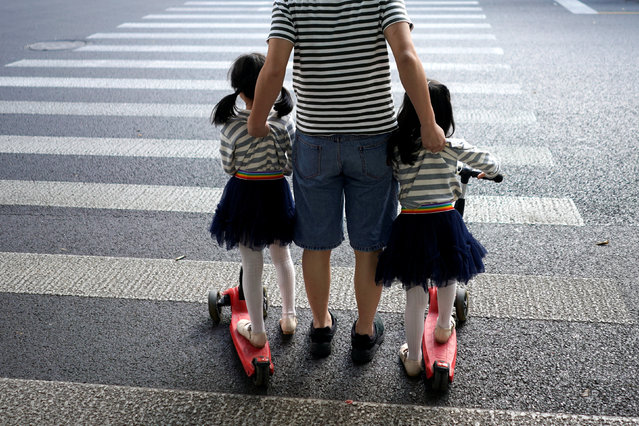 A father crosses a road with his twin daughters in Shanghai, China September 28, 2018. (Photo by Aly Song/Reuters)