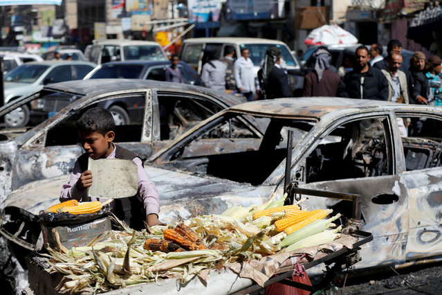 A boy sells grilled corn near cars damaged during recent clashes between Houthi fighters and forces loyal to Yemen's former president Ali Abdullah Saleh in Sanaa, Yemen December 5, 2017. (Photo by Khaled Abdullah/Reuters)