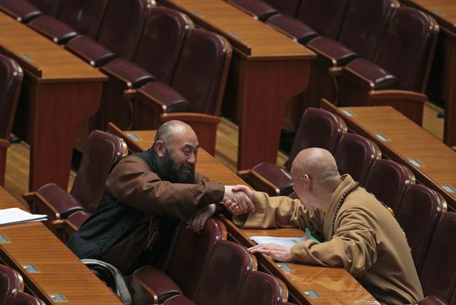 A delegate shakes hands with a monk delegate after the opening session of the Chinese People's Political Consultative Conference (CPPCC) at the Great Hall of the People in Beijing, March 3, 2015. REUTERS/Barry Huang