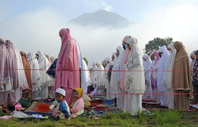 Indonesian Muslims attend a mass prayer session at Gunung Labu field as Mount Kerinci Volcano is seen in the background during Eid al-Fitr, marking the end of the holy fasting month of Ramadan, in West Kayu Aro, Kerinci, Jambi province, Indonesia, May 13, 2021. (Photo by Wahdi Septiawan/Antara Foto via Reuters)
