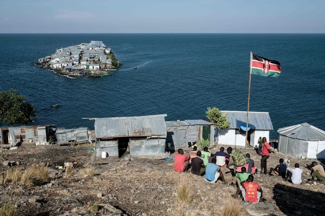 A Kenyan flag is seen at the base of Kenyan marine police on October 5, 2018 on Usingo island overlooking Migingo island which is densely populated by residents fishing mainly for Nile perch in Lake Victoria, the continent's largest lake, on the border of Uganda and Kenya. More than 500 people live on the island, which is barely 2,000-square-metres. A rounded rocky outcrop covered in metallic shacks, Migingo Island rises out of the waters of Lake Victoria like an iron- plated turtle. The densely- populated island is barely a quarter of a hectare large, its residents crammed into a hodge- podge of corrugated- iron homes, with seemingly little but a few bars, brothels and a tiny port to boast of. (Photo by Yasuyoshi Chiba/AFP Photo)