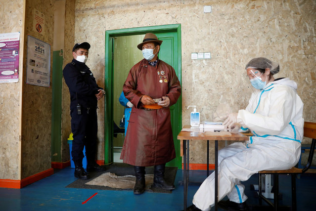 A man wearing a face mask following the coronavirus disease (COVID-19) outbreak waits at a polling station during the presidential election in Ulaanbaatar, Mongolia on June 9, 2021. (Photo by B. Rentsendorj/Reuters)