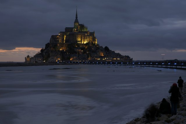 People sit on an embankment as the incoming high tide surrounds the Mont Saint-Michel 11th century abbey off France's Normandy coast  March 21, 2015. At the Mont Saint-Michel, where some of the biggest tides in the world occur, visitors earlier gathered to watch the tide disappear out of sight, exposing areas of beach and rock visible only every 18 years. (Photo by Pascal Rossignol/Reuters)