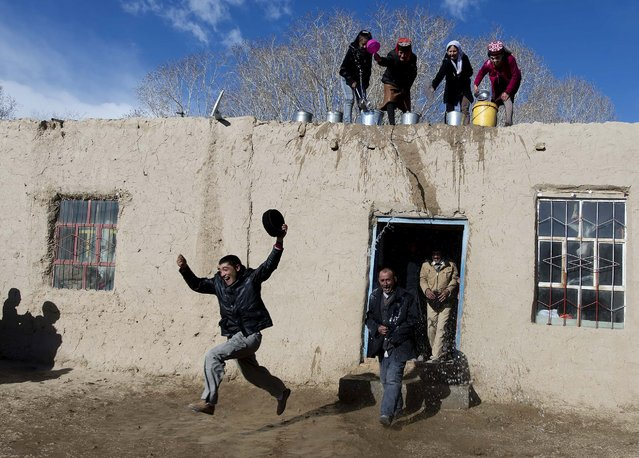 Tadjik women throw water on men from roof top as they take part in a festival celebration to welcome the coming Spring in Tadjik autonomous county, Kashgar, Xinjiang Uighur Autonomous Region, March 18, 2015. (Photo by Reuters/China Daily)