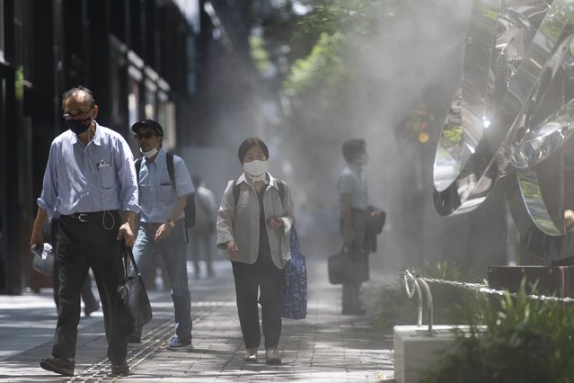 People wearing face masks to help curb the spread of the coronavirus walk on a sidewalk with a misting service in Tokyo Friday, July 16, 2021. (Photo by Hiro Komae/AP Photo)