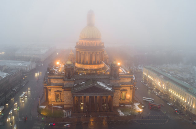 In this aerial view the city's famed St. Isaac's Cathedral is seen in fog in St.Petersburg, Russia, Monday, December 19, 2016. The temperature in St.Petersburg is plus 2C ( 35.6 °F). Southwest warm wind caused foggy weather in St. Petersburg on Monday. (Photo by Dmitri Lovetsky/AP Photo)