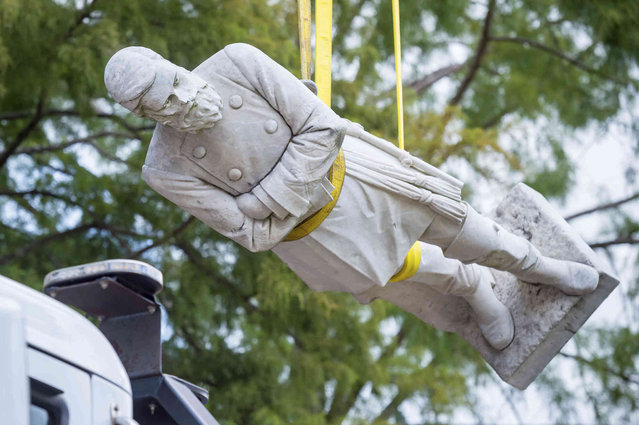 The statue of Confederate Gen. Alfred Mouton is removed on Saturday, July 17, 2021 in Lafayette, La.  The statue was moved from the front of city hall where it has stood for 99 years. (Photo by Scott Clause /The Daily Advertiser via AP Photo)