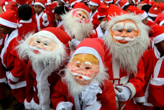 Indian schoolchildren dressed as Santa Claus pose as they take part in a Christmas event at a school in Chennai on December 5, 2018. (Photo by Arun Sankar/AFP Photo)