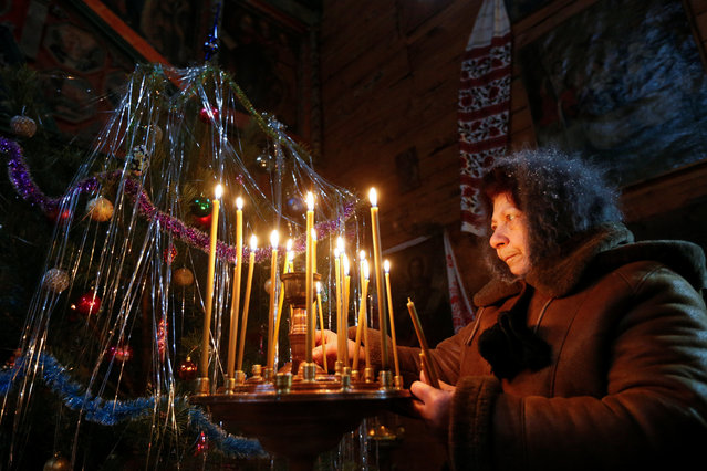 A woman places candles during a service to celebrate Orthodox Christmas in Kiev, Ukraine January 7, 2017. (Photo by Valentyn Ogirenko/Reuters)