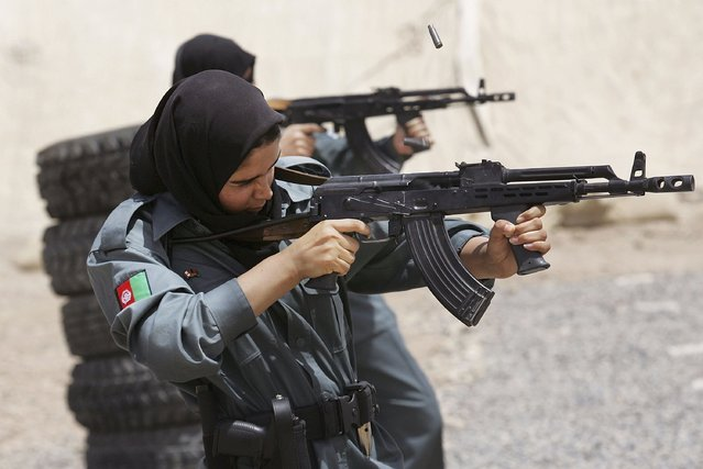Afghan police recruit, Masuma, 18, fires her AK-47 assault rifle during training at a regional police training center on June 6, 2006 in Kandahar, Afghanistan.  (Photo by John Moore/Getty Images)