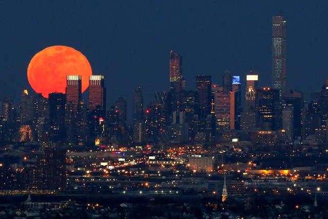 A full moon is seen as it rises over the New York City skyline seen from West Orange, N.J., Saturday, April 4, 2015. (Photo by Julio Cortez/AP Photo)