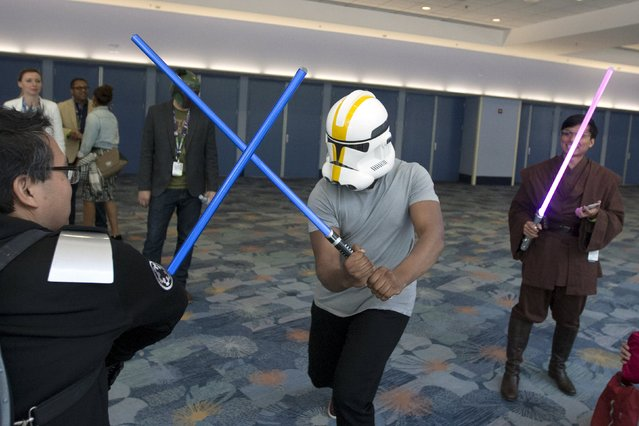 Star Wars: The Force Awakens cast member John Boyega disguises his identity with a helmet and engages unknowing fans in a light saber fight scene at the Star Wars Celebration convention in Anaheim, California, April 16, 2015. (Photo by David McNew/Reuters)