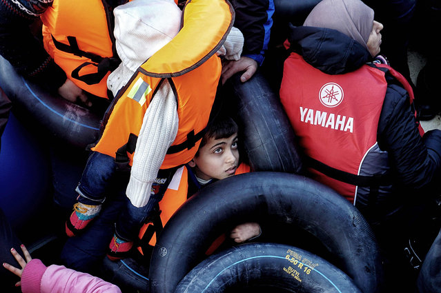 A picture taken on February 20, 2016 shows children among refugees and migrants on a rubber boat on their way from Turkey to the Greek northern island of Lesbos as they are rescued by Greek coast guards off Mytilene, Lesbos. (Photo by AFP Photo/Stringer)