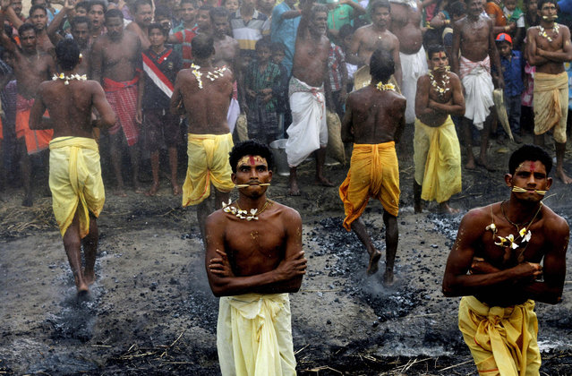Villagers walk on burning coal laid out in front of the temple of their village goddess on the last day of the Jhamu Yatra festival at Mendhasal village on the outskirts of Bhubaneswar, India, Tuesday, April 14, 2015. Faithful Hindu devotees offer various such rituals each year in the hope of winning the favor of their local deities. (Photo by Biswaranjan Rout/AP Photo)