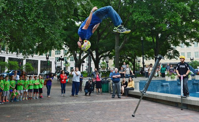 XPogo athlete Ryan O'Malley flips off his pogo stick as he completes a routine during his extreme pogo demonstration in Hemming Park, in Jacksonville, Fla., Thursday, April 16, 2015. (Photo by Bob Mack/The Florida Times-Union via AP Photo)