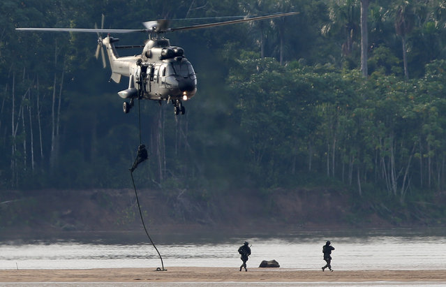 An army helicopter patrols the border with Colombia during a training to show efforts to step up security along borders, in Vila Bittencourt, Amazon State, Brazil, January 18, 2017. (Photo by Adriano Machado/Reuters)