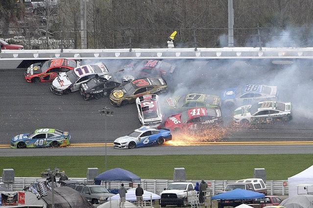 Martin Truex Jr. (19), Denny Hamlin (11), Kevin Harvick (4), Austin Dillon (3), Clint Bowyer (14), Erik Jones (20), Chase Elliott (9), Daniel Suarez (41), Ryan Newman (6), Alex Bowman (88) and Aric Almirola (10) are involved in a multi-car pileup during the NASCAR Clash auto race at Daytona International Speedway Sunday, February 10, 2019, in Daytona Beach, Fla. (Photo by Phelan M. Ebenhack/AP Photo)