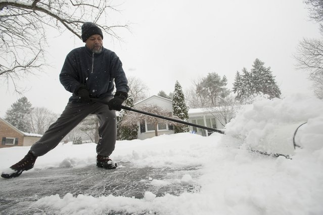 Rick Gibson shovels the snow from his neighbor's driveway on West Kalong Circle in Southfield, Michigan on Sunday, January 5, 2014, as metro Detroit digs out from a severe winter snow storm. (Photo by David Guralnick/AP Photo/The Detroit News)