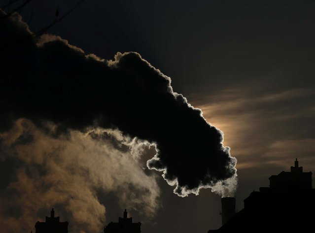 Smoke from a chimney is silhouetted against the rising sun in Harbin, China, on January 6, 2014. The fireworks display that had been held every year of the Harbin Ice and Snow Sculpture Festival on its opening night was cancelled this year, with organizers citing Harbin's bad air as a reason. In November of last year, alarming levels of smog caused Harbin, a city of 11 million people, to effectively shut down with schools suspending classes and the local airport temporarily closing. (Photo by Kim Kyung-Hoon/Reuters)