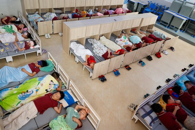 Students sleep on folding beds during the noon break at a primary school on September 7, 2021 in Jingning She Autonomous County, Lishui City, Jiangxi Province of China. (Photo by Lu Suren/VCG via Getty Images)
