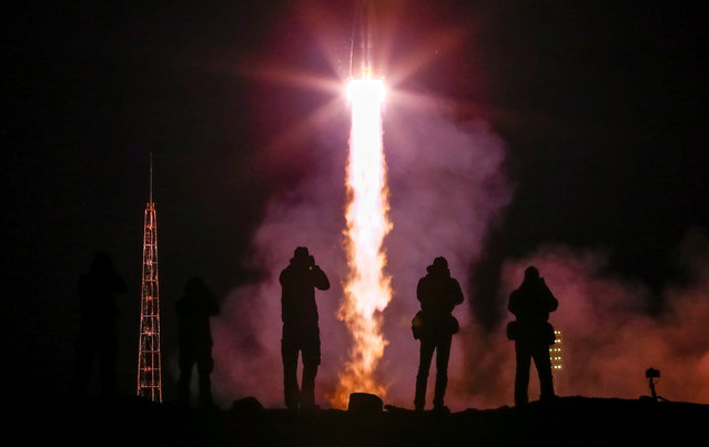 Photographers take pictures as the Soyuz MS-12 spacecraft carrying the crew formed of Aleksey Ovchinin of Russia, Nick Hague and Christina Koch of the U.S. blasts off to the International Space Station (ISS) from the launchpad at the Baikonur Cosmodrome, Kazakhstan March 15, 2019. (Photo by Shamil Zhumatov/Reuters)