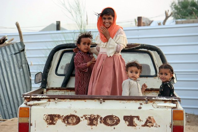 Children ride on the back of a truck at a camp for internally displaced people (IDPs) in Marib, Yemen on September 9, 2021. (Photo by Ali Owidha/Reuters)