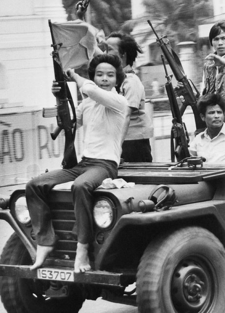 In this May 4, 1975 file photo, a youth waves a weapon and a Provisional Revolutionary Government (PRG) flag as he joins PRG troops on a jeep on Tu Do street in Saigon. (Photo by Matt Franjola/AP Photo)