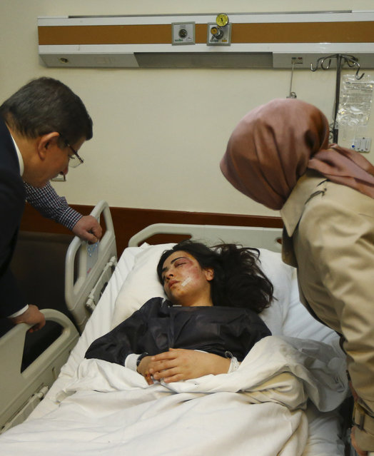 Turkey's Prime Minister Ahmet Davutoglu, left, accompanied by his wife Sare, right, visits a victim of Sunday's blast at a hospital in Ankara, Monday, March 14, 2016. Davutoglu said authorities had detained 11 people in connection with bombing and had reached strong indications that the attack was carried out by the rebels of the Kurdistan Workers' Party, or PKK.  The blast on Sunday killed dozens of people and wounded scores of others. (Photo by Hakan Goktepe/Prime Minister's Press Service, Pool Photo via AP Photo)
