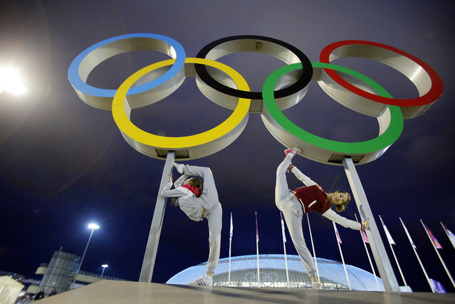 Russian dancers who will be performing at the opening ceremony pose with the Olympic rings as their friend photographs them, ahead of the 2014 Winter Olympics, Thursday, February 6, 2014, in Sochi, Russia. (Photo by Wong Maye-E/AP Photo)