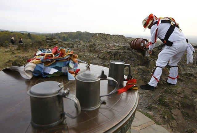 A Leicester Morrisman fills his tankard with beer between dances during May Day celebrations at Bradgate Park in Newtown Linford, Britain May 1, 2015. (Photo by Darren Staples/Reuters)