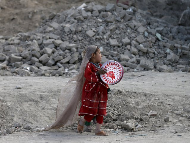 An Afghan girl plays a tambourine outside her house in Kabul, Afghanistan April 27, 2015. (Photo by Mohammad Ismail/Reuters)