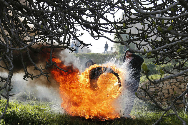 Palestinian protesters kick a burning tire during clashes with Israeli security forces on March 18, 2016, following a demonstration in solidarity with Palestinian prisoners held in Israeli jails, outside the compound of the Israeli-run Ofer prison near Betunia in the occupied West Bank. (Photo by Abbas Momani/AFP Photo)