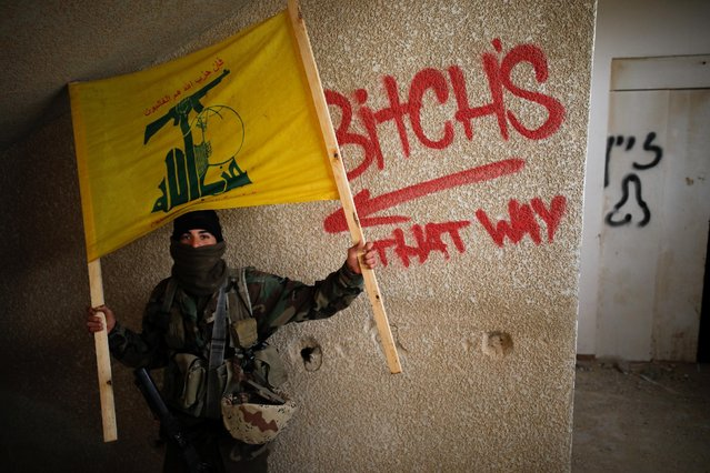 An Israeli soldier from the Nahal Infantry Brigade playing the role of the enemy, holds a mock Hezbollah flag, as he takes part in an urban warfare drill in an abandoned hotel in Arad, southern Israel February 8, 2017. (Photo by Amir Cohen/Reuters)